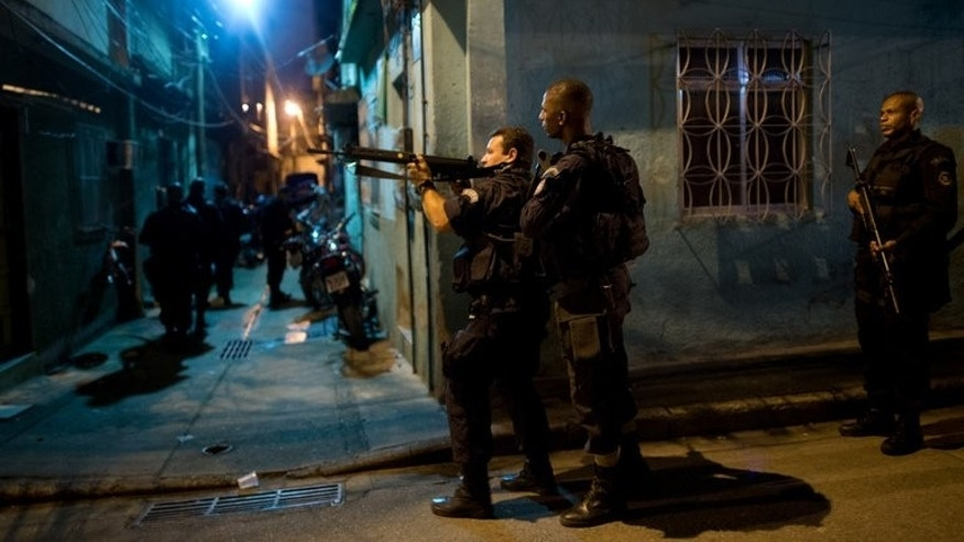 Brazilian BOPE police elite unit personnel patrol during an operation at Caju shantytown in Rio de Janeiro, Brazil, early morning March 3, 2013. Some 180 elite Brazilian police officers deployed into a drug-infested slum complex in northern Rio on Monday in order to prepare the way for a permanent presence there.