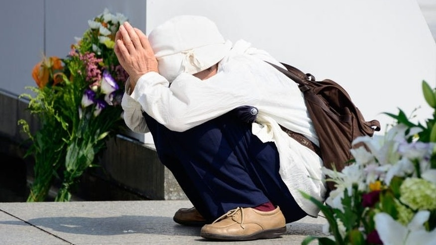 An elderly woman prays for victims of the 1945 atomic bombing of Hiroshima in front of the cenotaph at the Peace Memoral Park in Hiroshima on August 5, 2013. Hiroshima is marking the 68th anniversary of the atomic bombing on August 6, 2013.