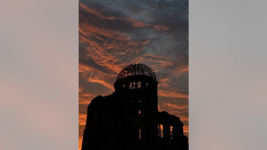 The Atomic Bomb Dome is seen in silhouette during sunset over the Peace Memoral Park in Hiroshima on August 5, 2013.