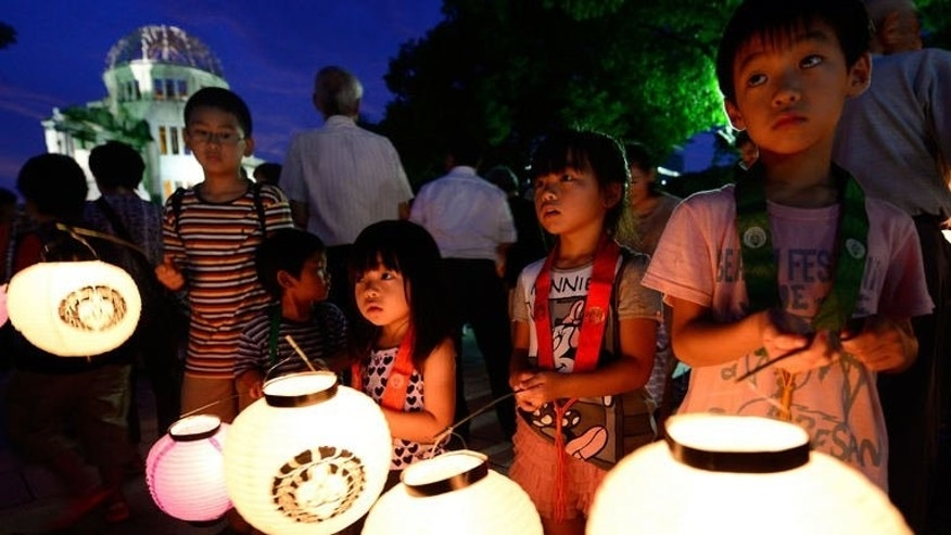 Children carry lanterns to pray for atomic bombing victims in front of the Atomic Bomb Dome at the Peace Memoral Park in Hiroshima on August 5, 2013.