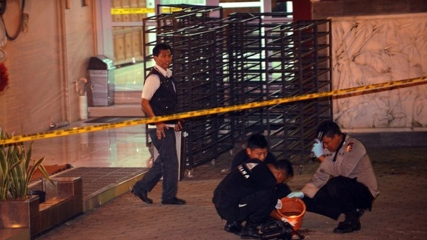 Police investigators gather evidence inside the compound of Ekayana Buddhist Centre in Jakarta, early dawn of August 5, 2013, after an explosive device went off at the temple the evening before, injuring one person. A second bomb was also set but only emitted smoke and failed to go off, according to police.