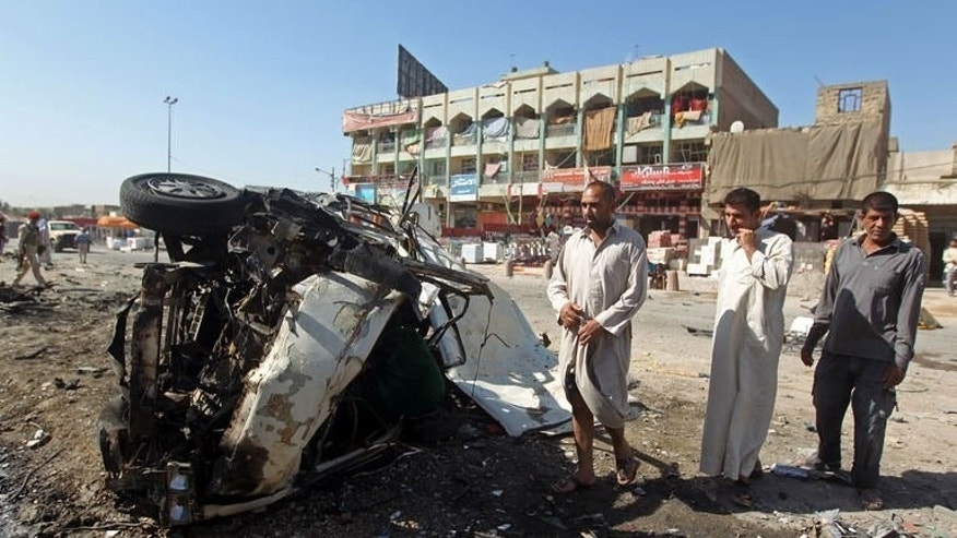 Iraqis inspect the site of a car bomb explosion in the impoverished district of Sadr City in Baghdad on July 29, 2013. Iraqi forces killed six suspected Al-Qaeda militants during an operation north of Baghdad on Monday, while two soldiers and seven civilians died in attacks, officials said.