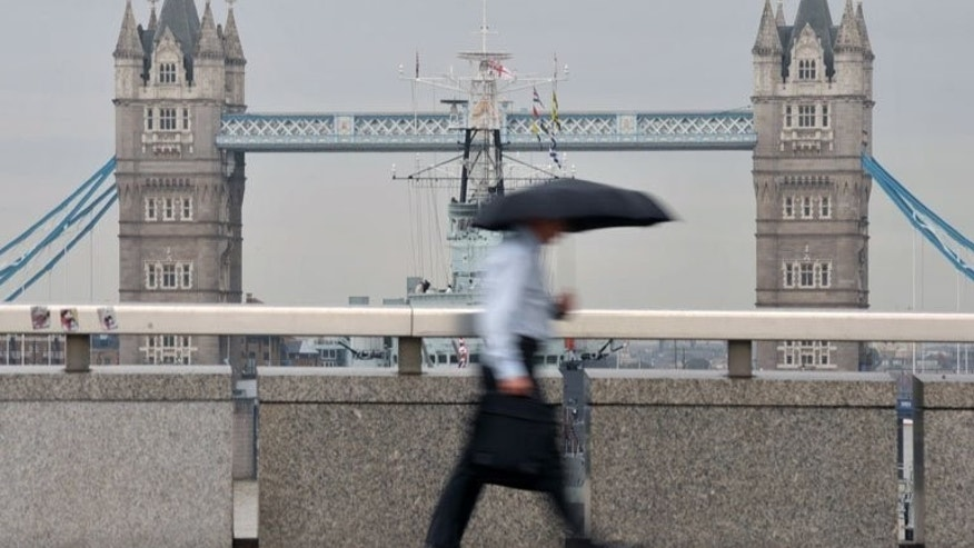 A city worker walks over London Bridge in central London. London shares closed lower on Monday as shares in HSBC tumbled after the global banking giant posted weaker-than-expected profits, traders said.