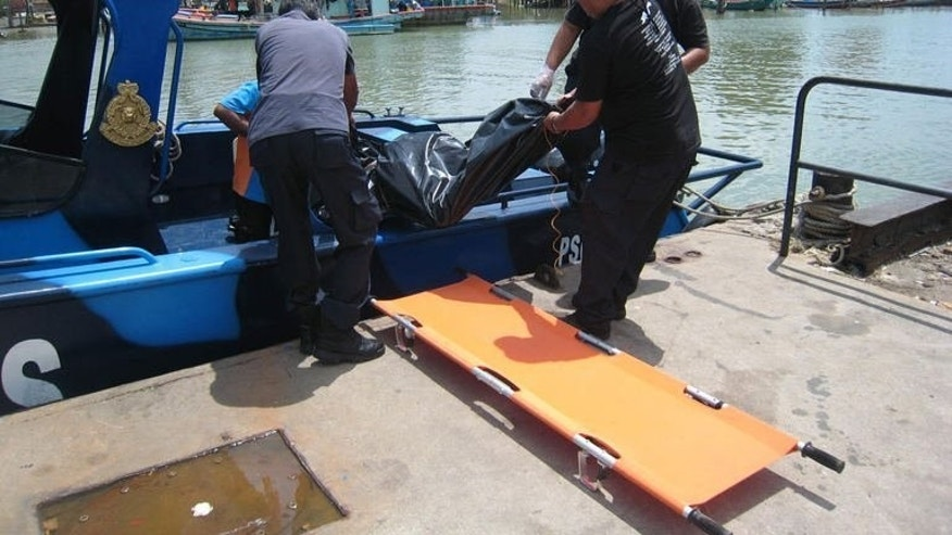 Malaysian officials remove a body from their rescue vessel in Tanjung Sedili, on August 4, 2013. Rescuers found a fourth body at sea on Monday as authorities said they may soon end the search for 36 other Indonesians missing after their boat sank on the way home to celebrate Eid al-Fitr.