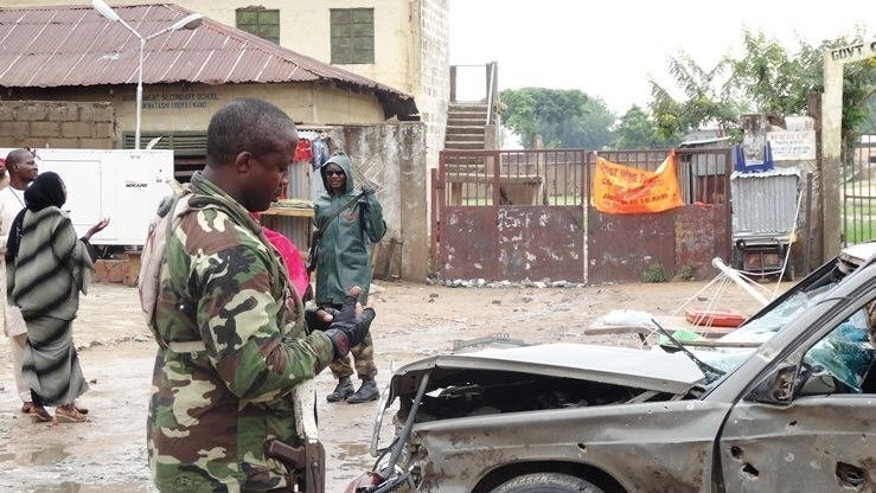 A soldier stands near a badly-damaged car at the scene of an explosion in Kano, northern Nigeria on July 30, 2013. Clashes between Nigeria's military and Islamist extremist group Boko Haram in two northeastern towns have left at least 35 people dead, most of them insurgents, the army said on Monday.