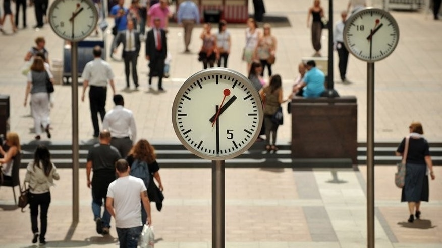 City workers walk past clocks in Canary Wharf, east London, on August 5, 2011. The number of workers on zero-hours contracts in Britain could be one million - four times as high as official estimates, according to new figures.