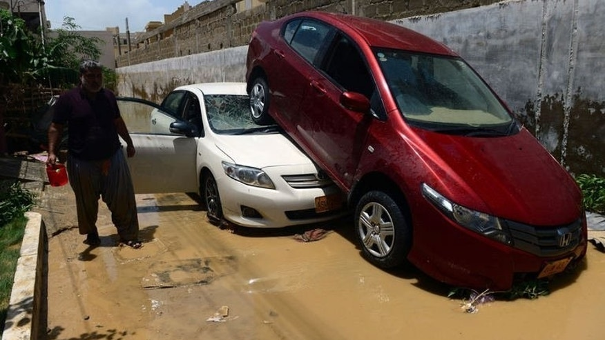 Damaged vehicles pictured in the aftermath of floods in a residential area of Karachi on August 5, 2013. Monsoon rain and floods have killed at least 58 people across Pakistan and affected tens of thousands of others, officials said Monday, warning of more rain to come.