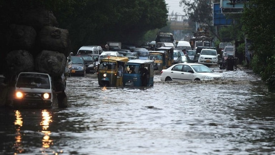 Pakistani motorists drive their vehicles along a flooded street in Karachi on August 3, 2013. Monsoon rain and floods have killed at least 58 people across Pakistan and affected tens of thousands of others, officials said Monday, warning of more rain to come.