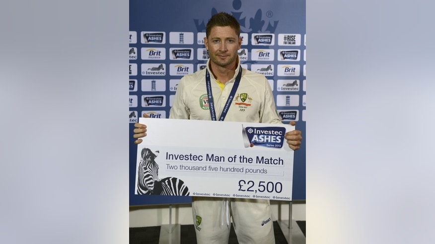 Australia's captain Michael Clarke holds the man of the match cheque after their third Ashes Test match finished in a draw and England retained the Ashes, at Old Trafford cricket ground in Manchester, on August 5, 2013.