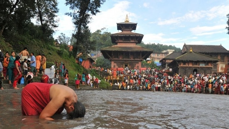 This file photo shows a Hindu devotee taking a holy bath and preforms a ritual near the Gokarneswar Mahadev Temple at Gokarna, on the outskirts of Kathmandu, on August 29, 2011. Six pilgrims drowned in northeastern Nepal on Monday while trying to cross a rain-swollen river, becoming the latest casualties of heavy monsoon downpours.