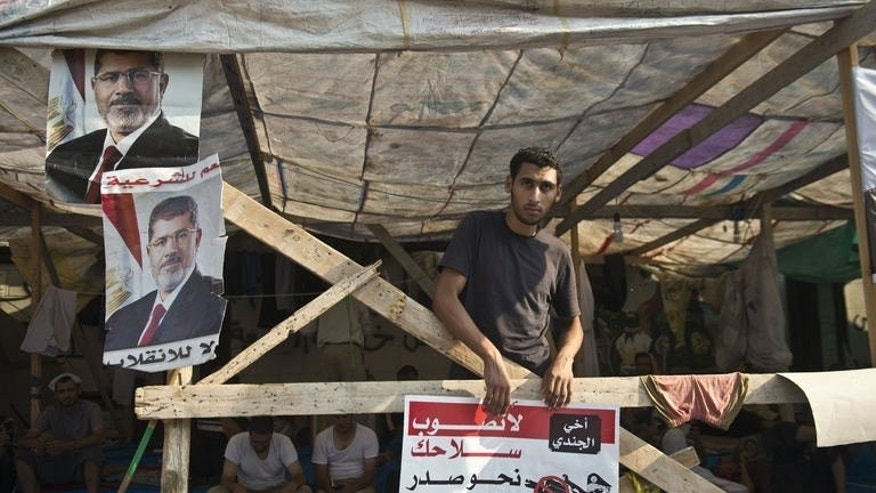 An Egyptian supporter of deposed president Mohamed Morsi holds a poster criticising the army during a sit-in outside Rabaa al-Adawiya mosque in Cairo on August 4, 2013.