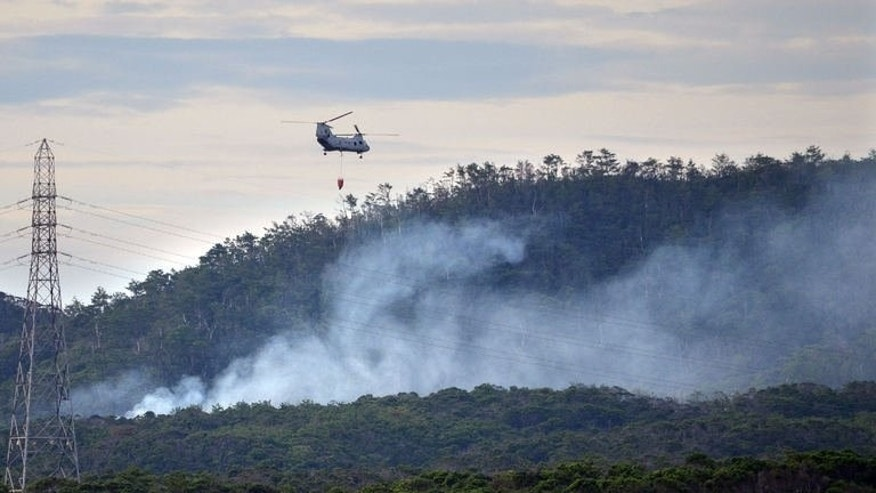 A US military helicopter flies on a fire fighting operation after a military helicopter crashed on a mountain in Camp Hansen in Ginoza village in Okinawa on August 5, 2013. The HH-60 helicopter was carrying four people, with three confirmed to be safe and the fourth taken hospital, a Japanese defence ministry official said.