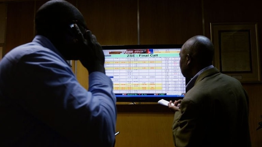"Members of the media look at a screen at Zimbabwe's Stock Exchange in Harare on August 5, 2013. Zimbabwe's defeated presidential candidate Morgan Tsvangirai prepared to mount a legal and political challenge against the ""sham"" election that looks set to extend Robert Mugabe's 33-year rule."