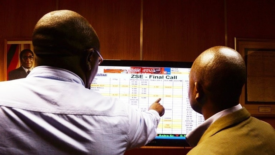 Members of the media look at a screen at Zimbabwe's Stock Exchange in Harare on August 5, 2013. Zimbabwe's main stock market index fell 11 percent today in its first trading day since official results confirmed President Robert Mugabe (portrait on wall at L) would extend his 33 years in power after trouncing Prime Minister Morgan Tsvangirai, who is contesting the outcome. AFP PHOTO / ALEXANDER JOE