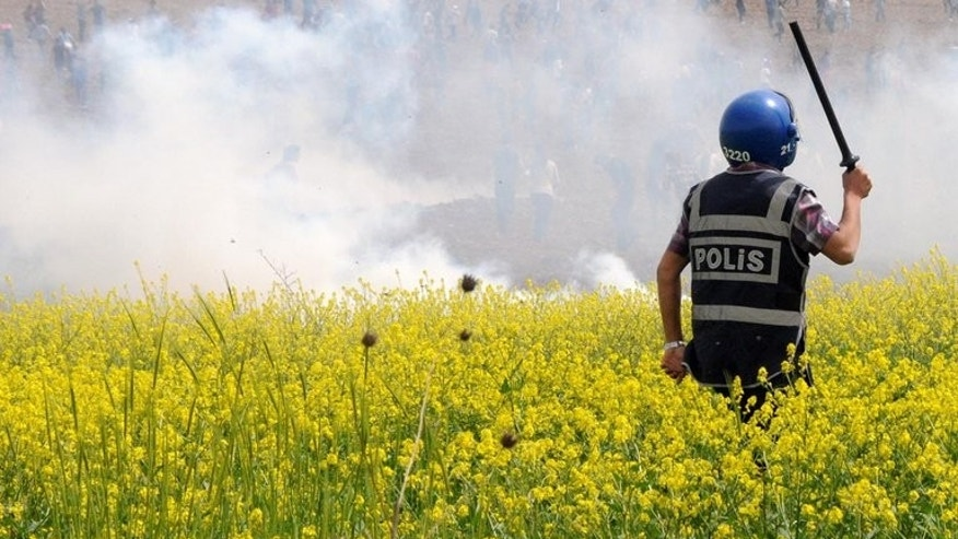 Turkish riot policemen and soldiers disperse Kurdish protesters in a field on April 9, 2013 near Dicle University in Diyarbakir. After embarking on a peace process with Kurdish rebels in Turkey, Ankara is now softening its position on the increasingly autonomous Kurdish minority in war-torn neighbouring Syria, analysts say.