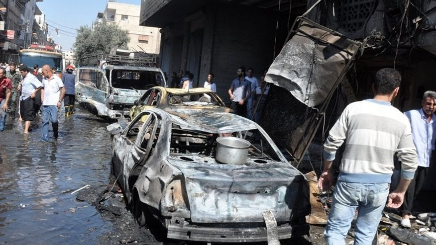 Syrians walk past a burned-out car after an attack on July 25, 2013 in the Jaramana suburb in southeast Damascus. A bomb killed 10 people in Jaramana on Tuesday, the latest in spate of blasts to hit the mainly Christian and Druze district, state television said.