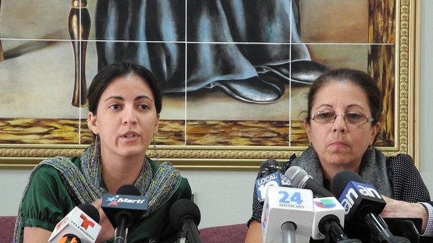"The daughter and widow of the late Cuban dissident Oswaldo Paya, Rosa Maria Paya (left) and Ofelia Acevedo, give a press conference in Miami, Florida, on June 18th, 2013. The family of late Cuban dissident Oswaldo Paya will launch a lawsuit in Spain after a Spanish politician said he did not die in a car crash but was ""assassinated"" by Cuba's secret services, Paya's brother said Tuesday."