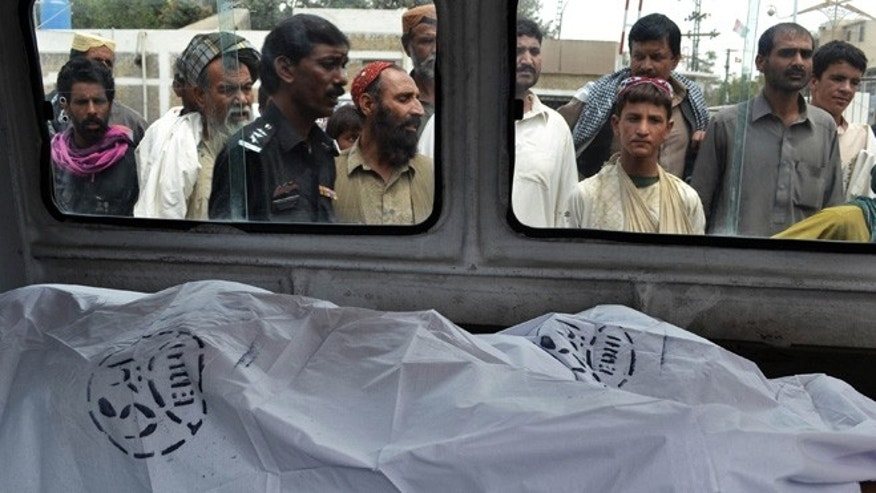 Aug. 6, 2013: People look at the lifeless bodies of victims shot by gunmen at a local hospital in Quetta, Pakistan.