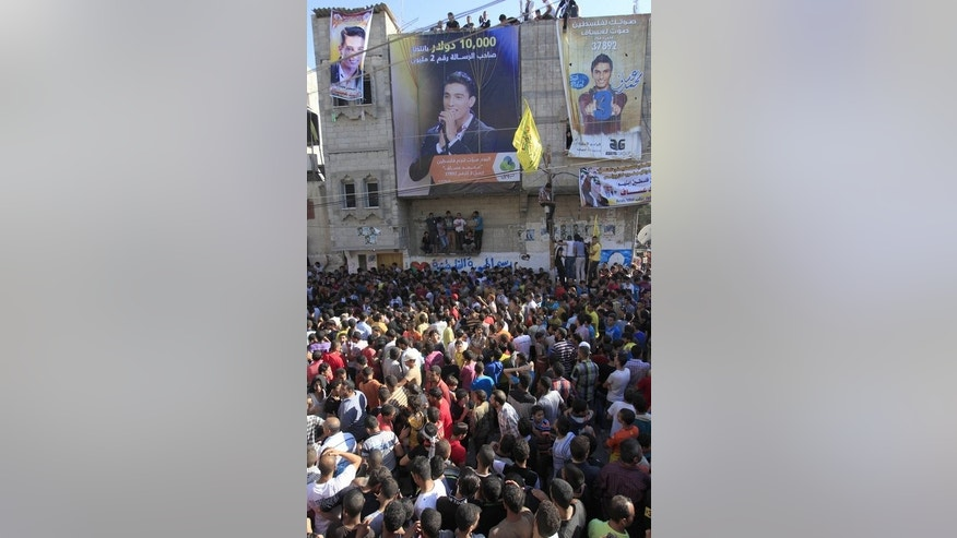 "People gather for the arrival of Palestinian ""Arab Idol"" Mohammed Assaf in front his home in Khan Yunis town in the southern Gaza Strip on June 25, 2013. Israel has authorised the young winner of the Arab Idol talent competition to move from the Gaza Strip to the West Bank as a ""humanitarian gesture,"" an official said Tuesday."