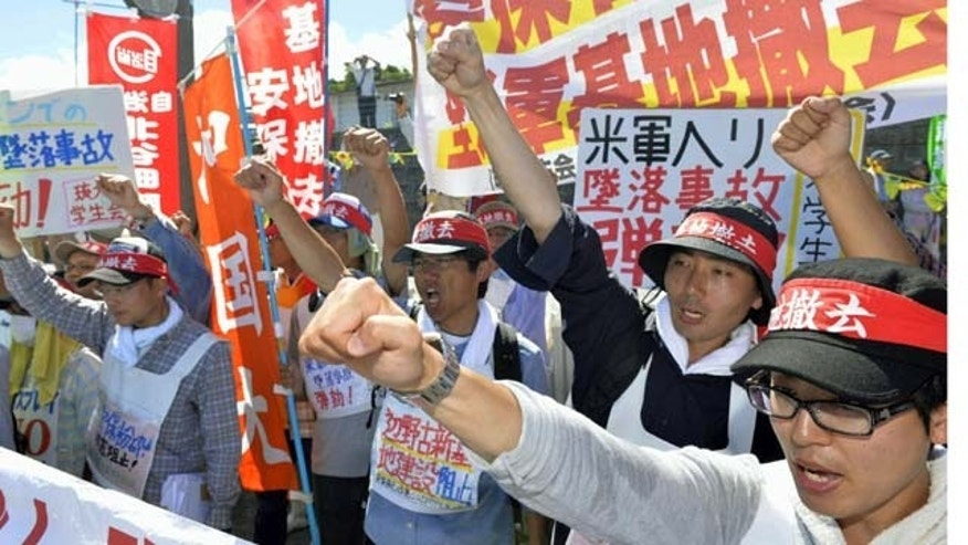 August 6, 2013: Protesters chant slogans against Monday's accident of a U.S. military helicopter crash and planned additional deployment of Osprey transport aircraft in front of a gate to U.S. Marine Corps Futenma Air Station in Ginowan, Okinawa, southwestern Japan. (AP Photo)