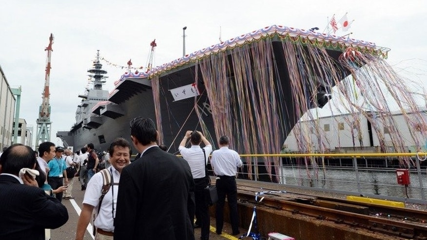 "Journalists look at Japan's new warship, the DDH183 Izumo, during the launch ceremony at the port in Yokohama on August 6, 2013. Japan unveiled its biggest warship since World War II on Tuesday, a $1.2 billion helicopter carrier aimed at defending territorial claims, drawing criticism from regional rival China which accused its neighbour of ""constant"" military expansion."