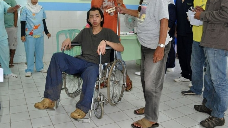 Tung Wei Jie (C), a Malaysian plantation worker held hostaged by Philippine Muslim extremists for almost a year, sits in a wheelchair inside a hospital for a medical check in Jolo town, Sulu province, on the southern island of Mindanao on August 6, 2013, shortly after his escape.
