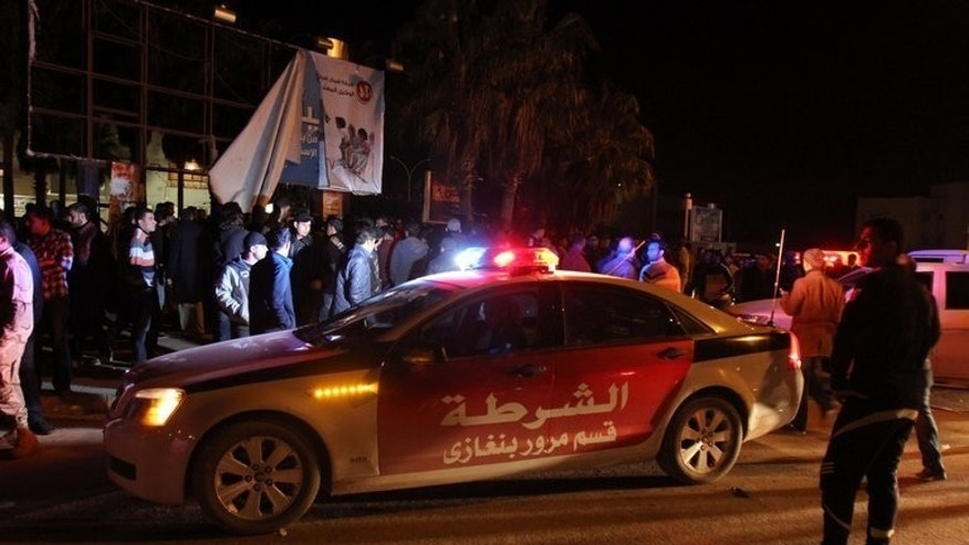 Libyan police gather at the scene of a bomb attack in the eastern city of Benghazi, on January 14, 2013. A bomb has exploded under a car in Libya's Benghazi killing the driver, a security official told AFP, the latest in a wave of violence to hit the restive city.