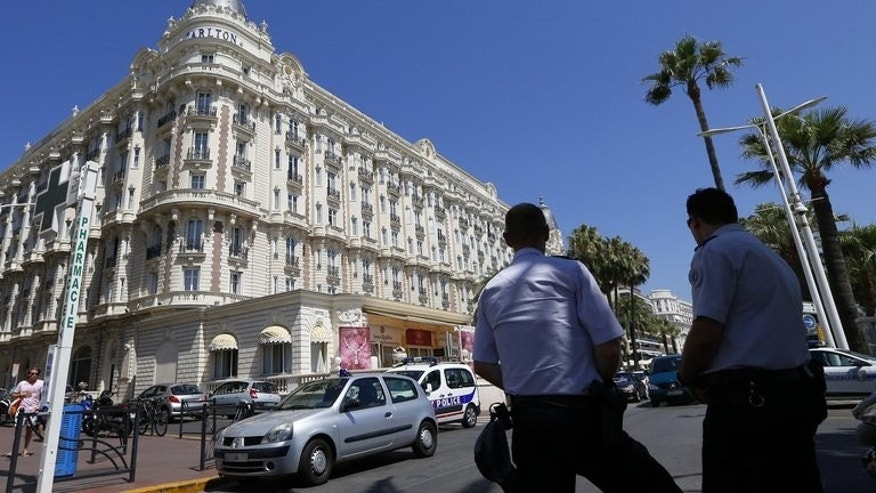 French police keep watch outside the Carlton Hotel on July 28, 2013 in Cannes, after an armed man robbed a jewellery exhibition. Insurers Lloyd's of London Tuesday offered up to 1.0 million euros ($1.3m) for information leading to the recovery of the stolen jewels worth an estimated 103 million euros.