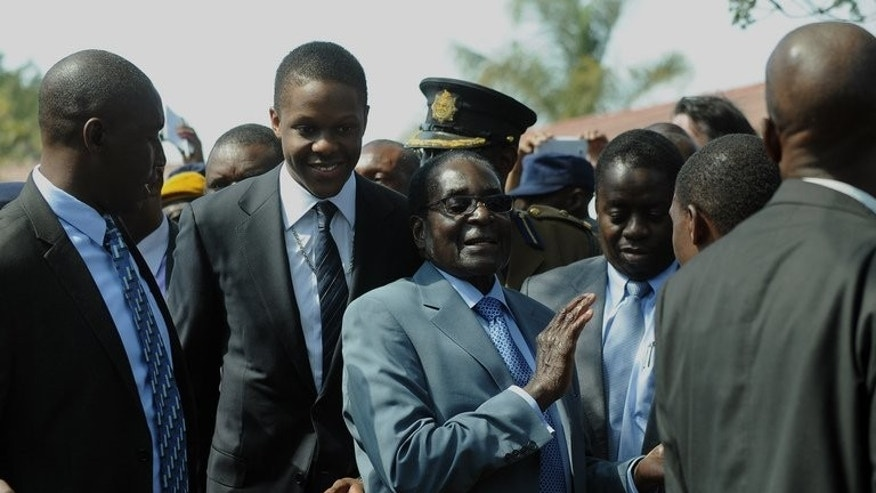 "Zimbabwe President Robert Mugabe (C) leaves after voting at a polling station in a school in Harare on July 31, 2013. Fresh from its landslide election victory President Robert Mugabe's party said Tuesday it would intensify the transfer of economic wealth to black Zimbabweans and overhaul the country's ""British"" education system."