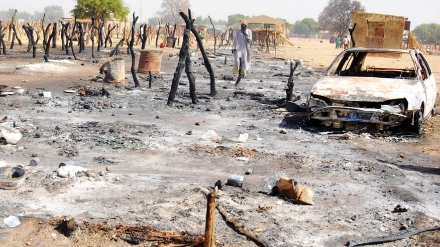 A man walks throught the scorched Tirken Shanu cattle market in the northeastern town of Potiskum on May 4 last year. Gunfire and explosions shook one northeastern Nigerian town Tuesday while soldiers slapped a round-the-clock curfew on another in the region hit by waves of insurgent attacks, the military and residents said.