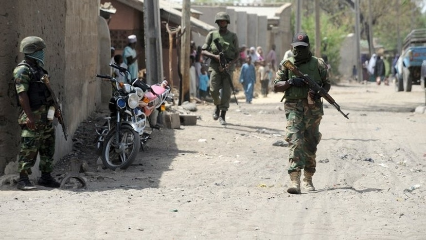 Soldiers patrol Baga in Borno State in April. Gunfire and explosions shook one northeastern Nigerian town Tuesday while soldiers slapped a round-the-clock curfew on another in the region hit by waves of insurgent attacks, the military and residents said.