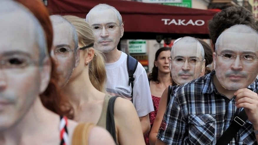 Wearing masks of Mikhail Khodorkovsky opposition activists take part in a demonstration marking the 50th birthday of the jailed former tycoon in St. Petersburg on June 26, 2013.