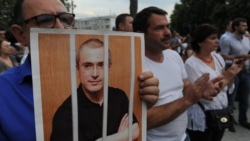 A demonstrator holds a portrait of Mikhail Khodorkovsky during a rally in Moscow, on June 26, 2013. Russia's supreme court on Tuesday began hearing an appeal by the jailed former oil tycoon against his second conviction which supporters say was ordered by the Kremlin.