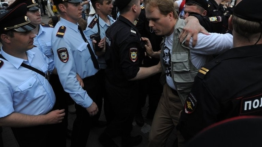 Police officers detain a supporter of Mikhail Khodorkovsky in Moscow, on June 26, 2013. Activists have expressed fear that new charges could yet be brought against Khodorkovsky as the Kremlin considers him such a dangerous potential opponent.