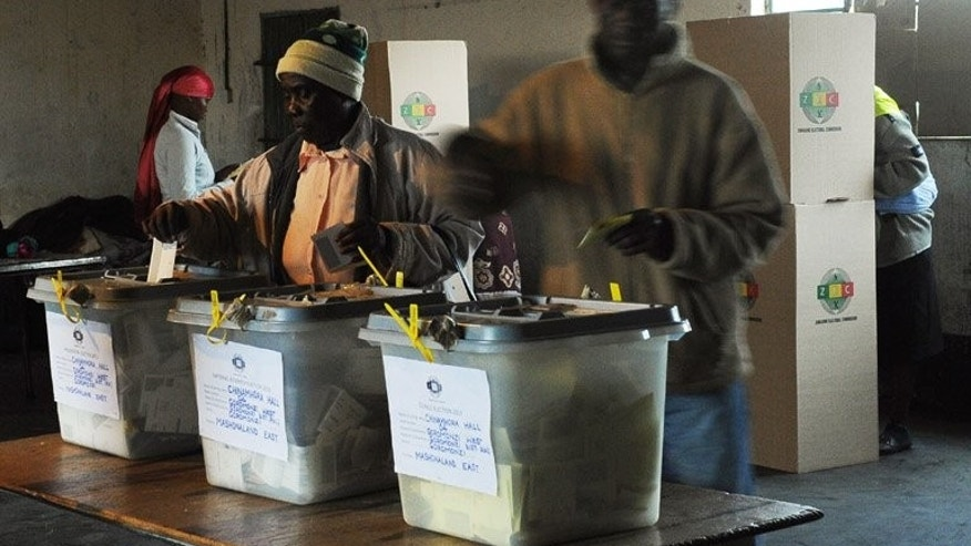 People cast their ballots at a polling station in Domboshava, 60km north of Harare, on July 31. A senior Zimbabwean election official said Tuesday he has resigned, just days after a colleague quit over the conduct of the vote that extended President Robert Mugabe's 33-year rule.