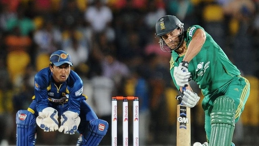 South African cricket captain Faf du Plessis (R) is watched by Sri Lankan wicketkeeper Dinesh Chandimal as he plays a shot as during the third and final Twenty20 cricket match at the Suriyawewa Mahinda Rajapakse International Cricket Stadium in the southern district of Hambantota on August 6, 2013.