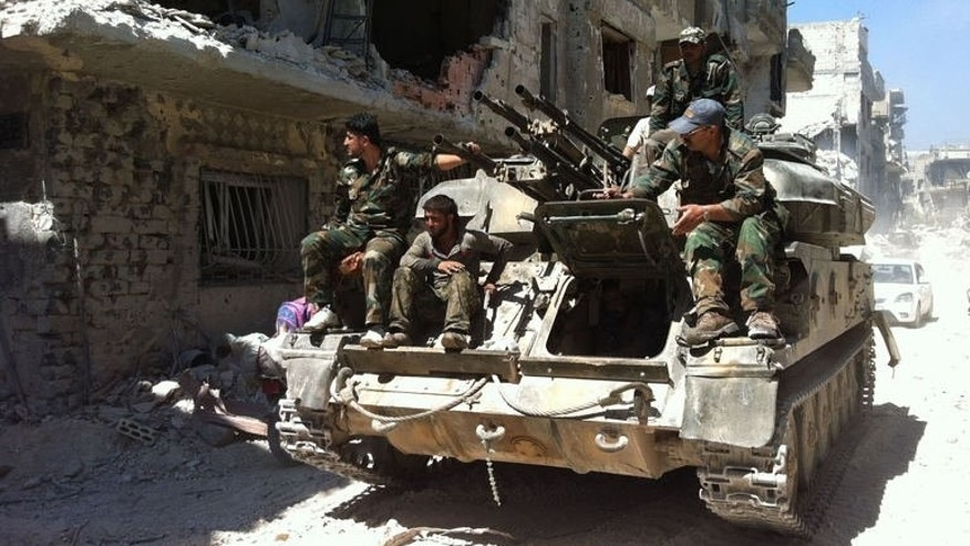 Soldiers loyal to the government sit patrol in a devastated street of the district of al-Khalidiyah, in the central Syrian city of Homs, July 29, 2013.