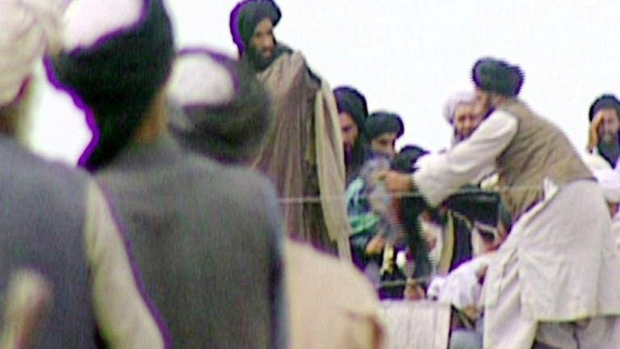 "A TV grab taken secretly by BBC Newsnight shows the Taliban's one-eyed spiritual leader Mullah Mohammed Omar (centre) during a rally of his troops in Kandahar before their victorious assault on Kabul in 1996. Taliban leader Mullah Omar on Tuesday dismissed elections due in Afghanistan next year as ""a waste of time"", posing a challenge to international efforts to ensure a credible poll."