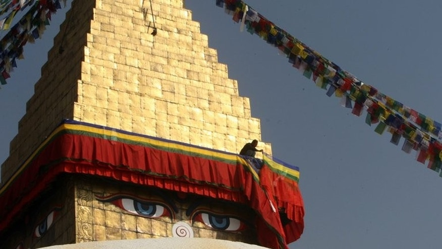 In this file photo, a Nepalese Buddhist is seen changing religious drapes at the Bouddhanath stupa in Kathmandu, on February 4, 2011. A Tibetan exile died after self-immolating at the Stupa on Tuesday morning, according to a local police official.