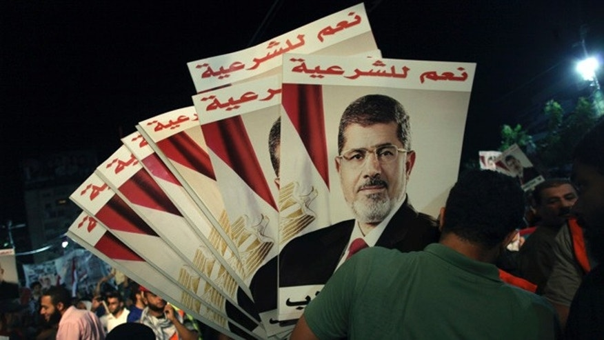 "Aug. 6, 2013: A supporter of Egypt's ousted President Mohammed Morsi holds his posters with Arabic writing which reads ""Yes for legality""; during a protest outside Rabaah al-Adawiya mosque, where protesters have installed a camp and hold daily rallies at Nasr City in Cairo, Egypt."
