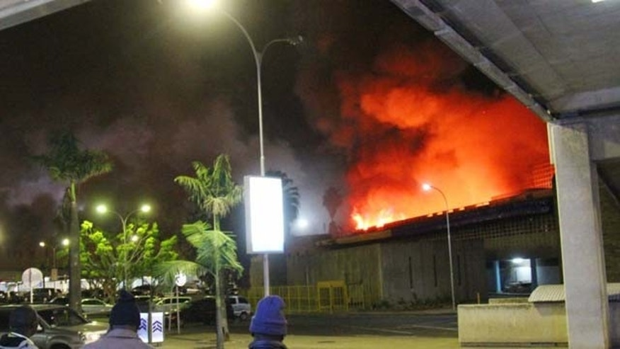 August 7, 2013: People watch a large blaze raging at the Jomo Kenyatta International Airport in Nairobi, Kenya early Tuesday. (AP Photo/Kyodo News)