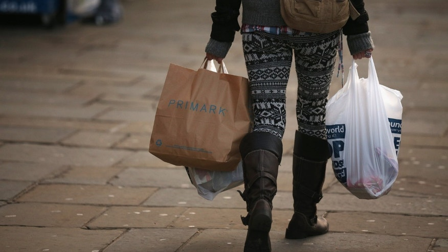 LONDON, ENGLAND - DECEMBER 05:  A woman carries several shopping bags from discount shops along Lewisham high street on December 5, 2012 in London, England. The Chancellor of the Exchequer George Osborne has stated that the United Kingdom's economy is still struggling during his autumn budget statement to Parliament.  (Photo by Oli Scarff/Getty Images)