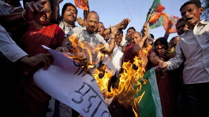 August 6, 2013: Activists of India's main opposition Bharatiya Janata Party (BJP) shout slogans and burn a representation flag of Pakistan during a protest against the death of five Indian army soldiers in cross-border exchanges, in Allahabad, India.