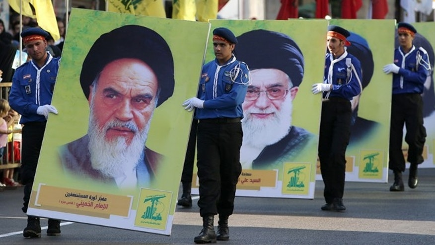 Hezbollah al-Mahdi scouts parade with big portraits of Iran's late leader Ayatollah Khomeini, foreground, and Iran's supreme leader Ayatollah Ali Khamenei, background, during an event for Jerusalem day or Al-Quds day, in the southern town of Nabatiyeh, Lebanon, Thursday, Aug. 1, 2013. The last Friday of the Islamic holy month of Ramadan is observed in many Muslim countries as Al-Quds day, as a way of expressing support to the Palestinians and emphasizing the importance of Jerusalem to Muslims. (AP Photo/Hussein Malla)