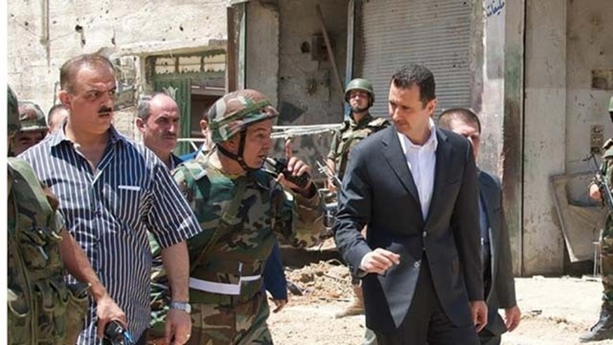 August 1, 2013: This image posted on the official Facebook page of the Syrian Presidency purports to show Syrian President Bashar Assad walking with soldiers with during Syrian Arab Army day in Darya, Syria (AP Photo)