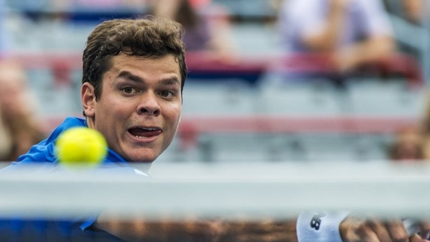 Milos Raonic of Canada returns the ball to Ernests Gulbis of Latvia during their quarterfinal Rogers Cup match on August 9, 2013 in Montreal. Raonic won 7-6 (7/3), 4-6, 6-4.