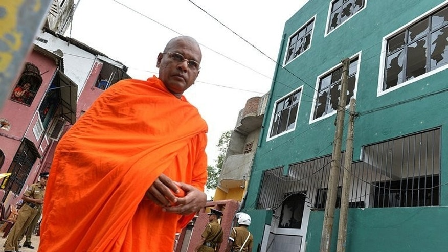 A Buddhist monk walks past a vandalized mosque in Colombo, on August 11, 2013. Sri Lankan police clamped a fresh curfew on a Colombo neighbourhood Sunday, a day after a Buddhist-led mob vandalised a mosque in an incident that raised religious tensions and US concern.
