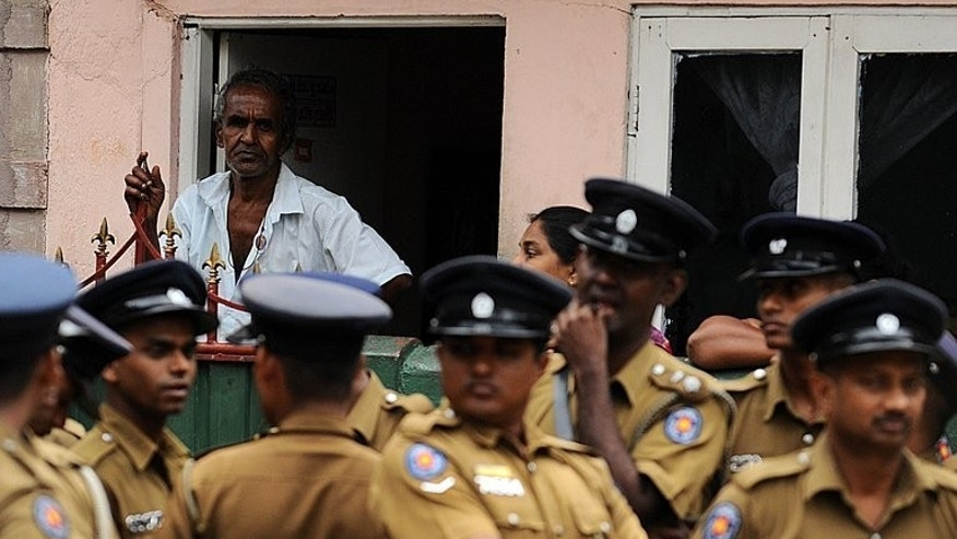 A Sri Lankan Muslim looks on as police officers investigate the scene of a vandalized mosque in Colombo, on August 11, 2013. Sri Lankan police clamped a fresh curfew on a Colombo neighbourhood Sunday, a day after a Buddhist-led mob vandalised a mosque in an incident that raised religious tensions and US concern.