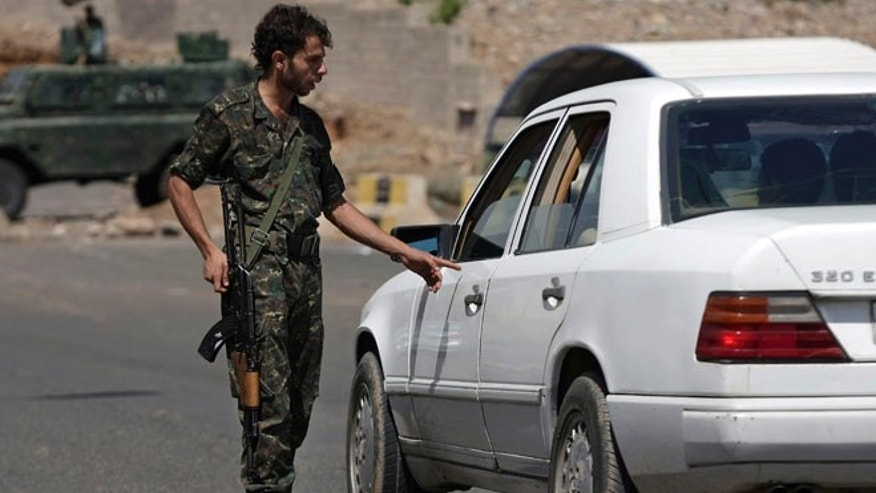Aug. 10, 2013: In this file photo, a Yemeni soldiers checks a car at a checkpoint on a street leading to the U.S. and British embassies in Sanaa, Yemen. Gunmen believed to be from Al Qaeda killed five Yemeni soldiers early Sunday, Aug. 11, 2013 at a checkpoint in a southern province, attacking the surprised soldiers who were guarding oil and gas projects in the Radhum area of Shabwa province a Yemeni official said.