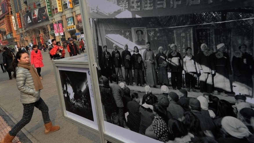 This file photo taken on February 21, 2013 shows a Chinese woman walking past an exhibition of Cultural Revolution era photos on display at the Wangfujing shopping street in Beijing. As a teenager radicalised by China's Cultural Revolution, Zhang Hongbing denounced his mother to the authorities. Two months later a firing squad shot her dead.